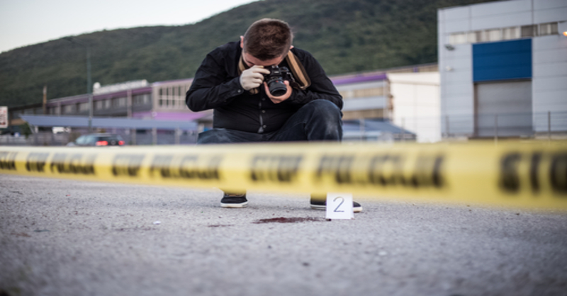 Blood Spatter Analyst Taking Pictures at a Crime Scene