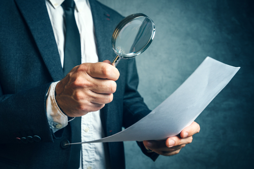 Person with magnifying glass reviewing paperwork