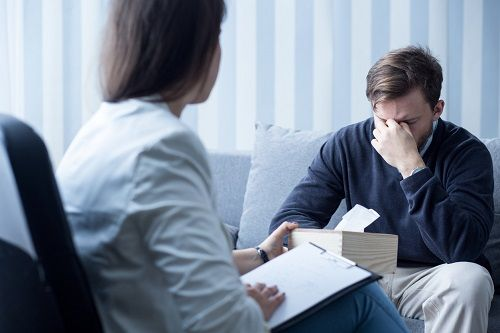 Woman offering man tissues in a therapy session