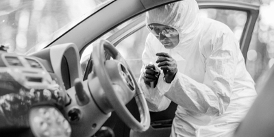 crime scene investigator collecting prints from car steering wheel