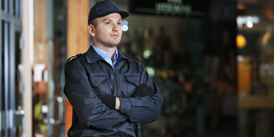 security professional standing guard outside guilding