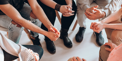 support group in meeting - close up on their hands in a circle