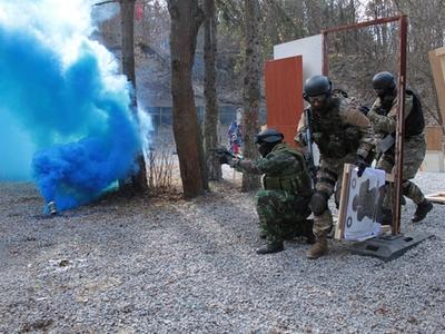 Men in camo running around blue smoke bomb