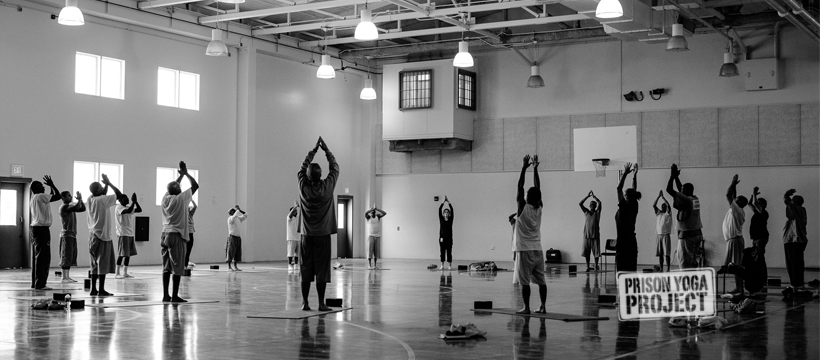 Group of men doing yoga in a gym