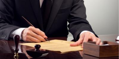 Businessman signing paper at a desk